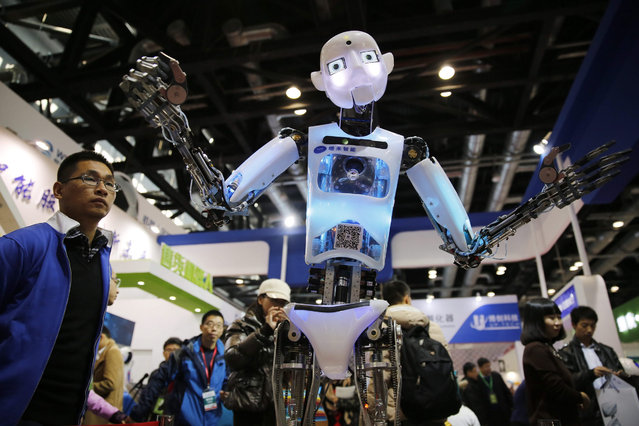 Visitors watch a robot on shown during the World Robot Conference at China national convention center in Beijing city, China, 23 November 2015. (Photo by Wu Hong/EPA)