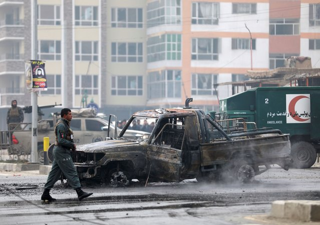 Afghan security personnel inspect the site of a bombing attack in Kabul, Afghanistan, Sunday, Decenber 20, 2020. The strong car bomb explosion rocked the capital Kabul city on Sunday morning, killing multiple people, said a government official. (Photo by Rahmat Gul/AP Photo)