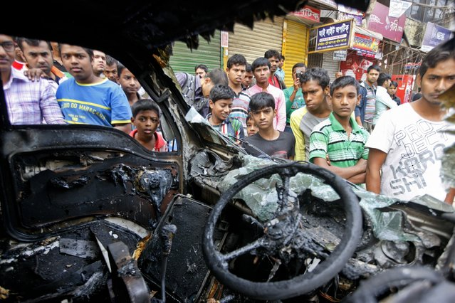 Bangladeshi people gather near a burnt vehicle, torched by Bangladesh Nationalist Party supporters and activists of Islami Chhatra Shibir, student wing of the Jamaat-e-Islami party,  in Dhaka, Bangladesh, Monday, January 5, 2015. (Photo by Suvra Kanti Das/AP Photo)