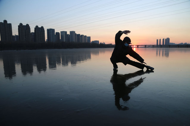 A man practices Tai Chi on the frozen Hunhe River at sunset on December 4, 2020 in Shenyang, Liaoning Province of China. (Photo by Zhu Huaqiang/VCG via Getty Images)