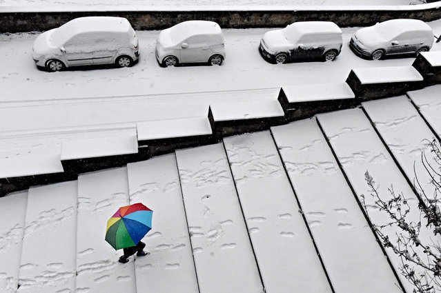 A person using an umbrella walks along a path as snow falls in Florence, Italy, 01 March 2018. A cold spell has reached central and eastern Europe with temperatures far below zero. (Photo by Maurizio Degl Innocenti/EPA/EFE)