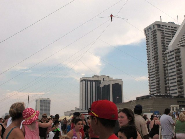 A crowd watches as daredevil Nik Wallenda walks a tightrope above the beach at Atlantic City on Thursday, Aug. 9, 2012. Officials say some 150,000 people witnessed the walk. (Photo by Geoff Mulvihill/AP Photo)