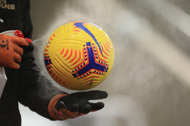 Ground staff disinfect a Premier League football before the English Premier League football match between Newcastle United and Leeds United at St James' Park in Newcastle-upon-Tyne, north east England on January 26, 2021. (Photo by Lindsey Parnaby/Pool via AFP Photo)