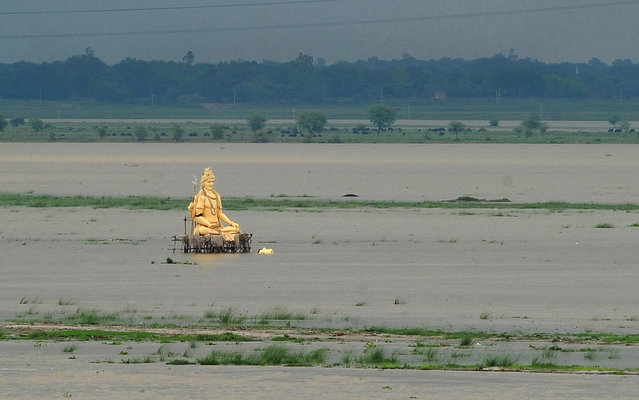A giant statue of Hindu god Lord Shiva is partially submerged in floodwaters near the Ganges river as the water level of the Ganges and Yamuna rivers rises in Allahabad on July 1, 2013. Construction along river banks will be banned in the devastated north Indian state of Uttarakhand amid concerns unchecked development fuelled June's flash floods and landslides that killed thousands, the state's top official said July 1. (Photo by Sanjay Kanojia/AFP Photo)