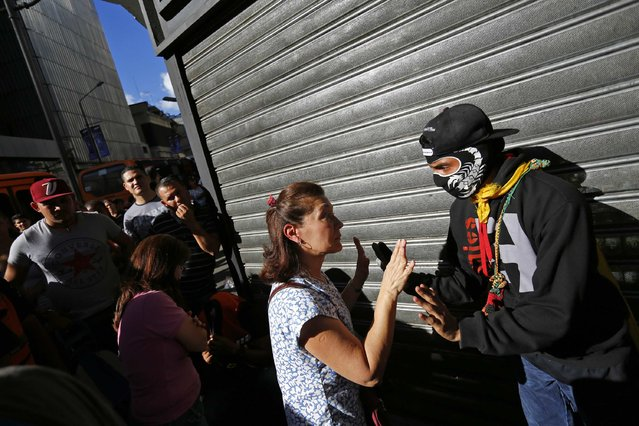 A demonstrator (R) who supports the opposition argues with a woman who was lining outside a supermarket to buy basic goods when it closed shortly for the day due to the ongoing protest in Caracas January 24, 2015. (Photo by Jorge Silva/Reuters)