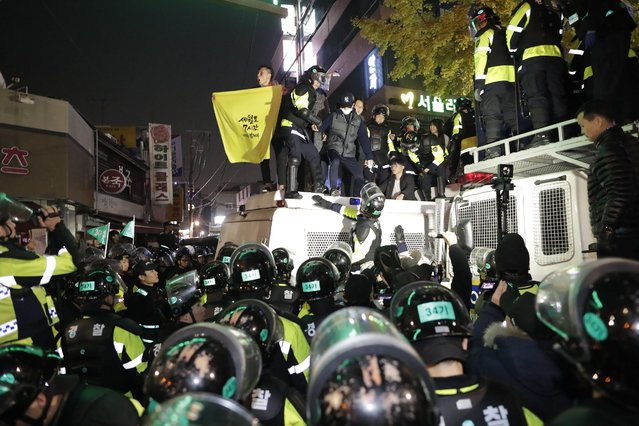 A South Korean man shout slogans on the police vehicle  during a protest against South Korean President Park Geun-Hye on a main street in Seoul, South Korea, 12 November 2016. The protesters gather to demand South Koreans President Park resignation after she has issued a rare public apology after acknowledging close ties to Choi Sun-sil, who is in the center of a corruption scandal. (Photo by Jung Byung-Hyuk/EPA)