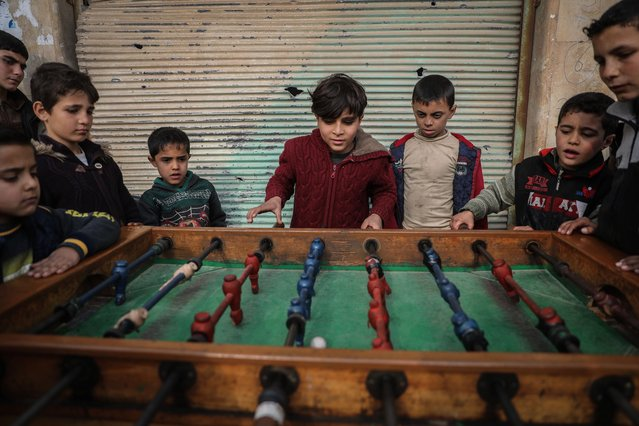Syrian children play table foosball amongst damaged buildings at the village of Afes, Syria on January 2, 2021. Residents of Afes started returning back to their homes after they were forced into internal displacement due to the intense bombing amid the Syrian Government's military campaign in North-western Syria. (Photo by Anas Alkharboutli/picture alliance via Getty Images)