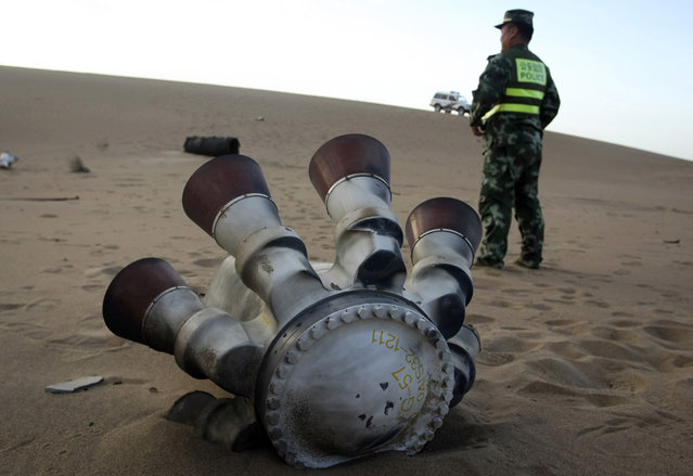 A policeman stands guard next to a component of the Shenzhou-10 manned spacecraft which was found in Badain Jaran Desert after the launch, in Alxa League, Inner Mongolia Autonomous Region, on June 12, 2013. (Photo by Reuters/Stringer via The Atlantic)