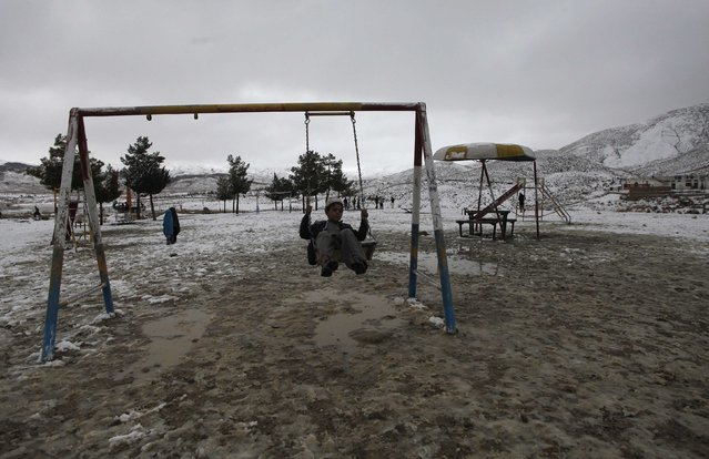 A boy plays on swing while visiting Hanna Lake after a snowfall on the outskirts of Quetta January 21, 2015. (Photo by Naseer Ahmed/Reuters)