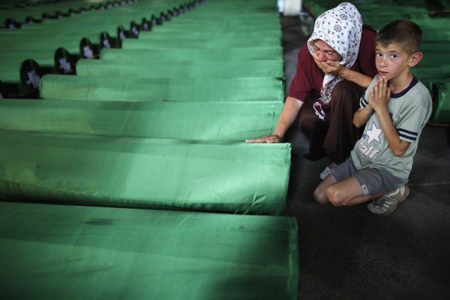 A Bosnian woman cries near the coffin of her relative, one of 409 newly identified victims of the 1995 Srebrenica massacre, in Memorial Center Potocari near Srebrenica July 10, 2013. The bodies of the recently identified victims will be transported to the memorial centre in Potocari where they will be buried on July 11 marking the 18th anniversary of the massacre in which Bosnian Serb forces commanded by Ratko Mladic killed up to 8,000 Muslim men and boys and buried them in mass graves. (Photo by Dado Ruvic/Reuters)