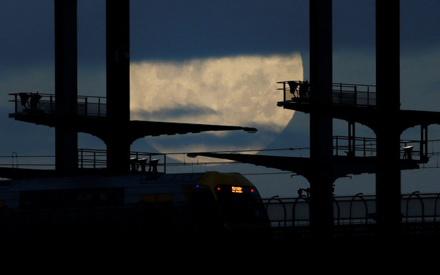 A commuter train en route to the suburb of Hornsby crosses on the Sydney Harbor Bridge under the Super Moon, November 14, 2016. (Photo by Jason Reed/Reuters)