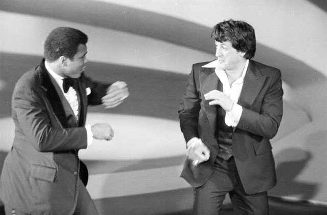 """Heavyweight champion Muhammad Ali, left, makes a suprise appearance on the Academy Awards show, staging a sparring with Sylvester Stallone, actor and screenwriter of the boxing drama """"Rocky"""", on March 28, 1977, in Los Angeles, California. (Photo by AP Photo)"""