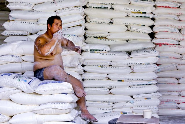 A porter smokes during a break at a flour wholesale market in Beijing, on July 18, 2013. (Photo by Jason Lee/Reuters)