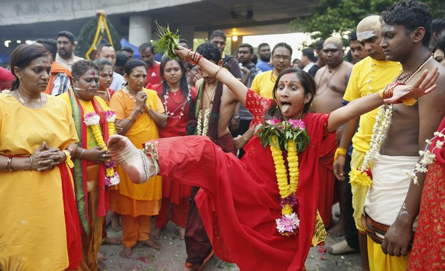 Hindu devotees go into a trance before starting their pilgrimage to the Batu Caves temple during Thaipusam in Kuala Lumpur February 2, 2015. Thousands of Hindus participate in the annual Hindu festival in which devotees subject themselves to painful rituals in a demonstration of faith and self punishment. Hindus believe they are cleansed of all sins and their misdeeds can be redeemed by observing prayers during Thaipusam. (Photo by Olivia Harris/Reuters)
