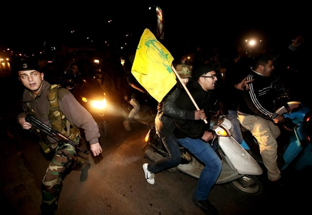 A Lebanese army soldier crosses a street past Hezbollah supporters riding their motorcycles and shouting slogans against a convoy carrying Syrian opposition fighters upon their arrival, at the Rafik Hariri International Airport, in Beirut, Lebanon, Monday, December 28, 2015. (Photo by Hussein Malla/AP Photo)