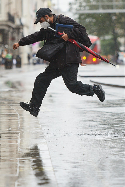A man leaps over a puddle on Oxford Street following heavy rain on October 02, 2020 in London, England. (Photo by Leon Neal/Getty Images)