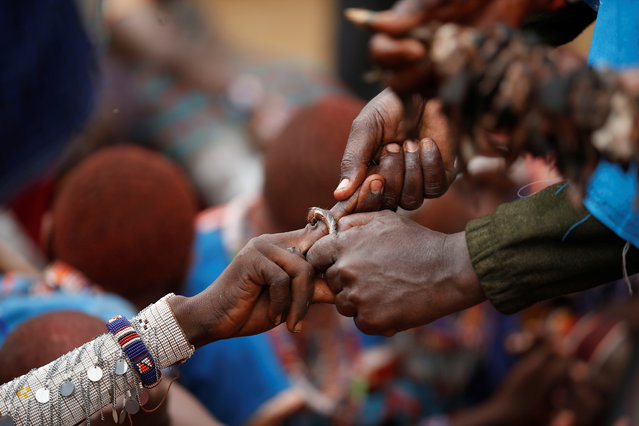 A Maasai elder places a ring made of a bull's leather on a boy's finger during an initiation into an age group ceremony near the town of Bisil, Kajiado county, Kenya on August 23, 2018. (Photo by Baz Ratner/Reuters)