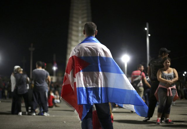 A mourner wears a Cuban flag on his shoulders as he attends a tribute to Cuba's late President Fidel Castro at Revolution Square in Havana, Cuba, November 29, 2016. (Photo by Edgard Garrido/Reuters)