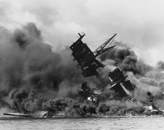 The forward superstructure of the sunken battleship USS Arizona burns after the Japanese raid on Pearl Harbor, December 7, 1941. (Photo by Reuters/U.S. Naval History and Heritage Command)