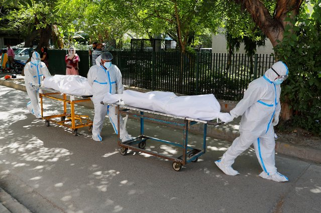 Health workers wearing personal protective equipment (PPE) carry bodies of people who were suffering from the coronavirus disease (COVID-19), outside the Guru Teg Bahadur hospital, in New Delhi, India, April 24, 2021. (Photo by Adnan Abidi/Reuters)