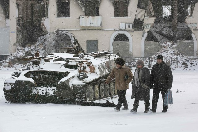 Locals walk past a destroyed Ukrainian army armoured personnel carrier in the town of Vuhlehirsk, about 10 km (6 miles) to the west of Debaltseve, February 16, 2015. (Photo by Baz Ratner/Reuters)