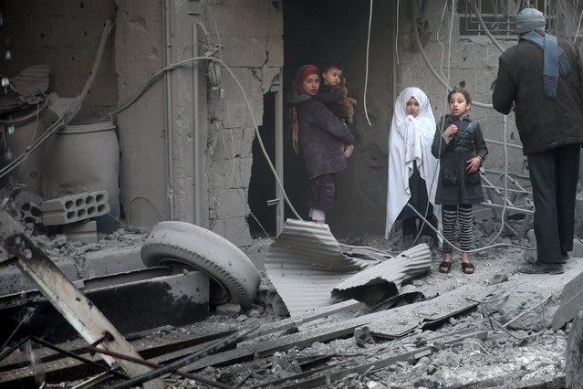Children inspect damage in a site hit by what activists said were airstrikes carried out by the Russian air force in the town of Douma, eastern Ghouta in Damascus, Syria January 10, 2016. (Photo by Bassam Khabieh/Reuters)