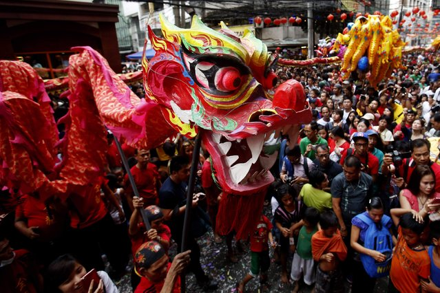 Revellers gather near lion dance performers to celebrate Lunar New Year at Manila's Chinatown February 19, 2015. (Photo by Erik De Castro/Reuters)