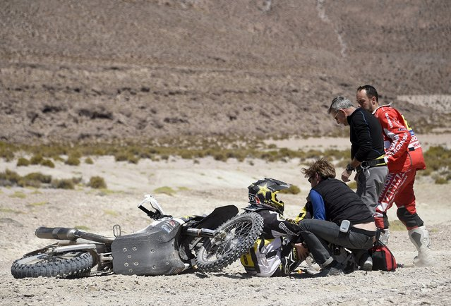 Husqvarna rider Ruben Faria of Portugal receives medical attention as KTM rider Gerard Farres Guell (R) of Spain approaches him after a fall during the sixth stage in the Dakar Rally 2016 near Uyuni, Bolivia, January 8, 2016. (Photo by Frank Fife/Reuters)