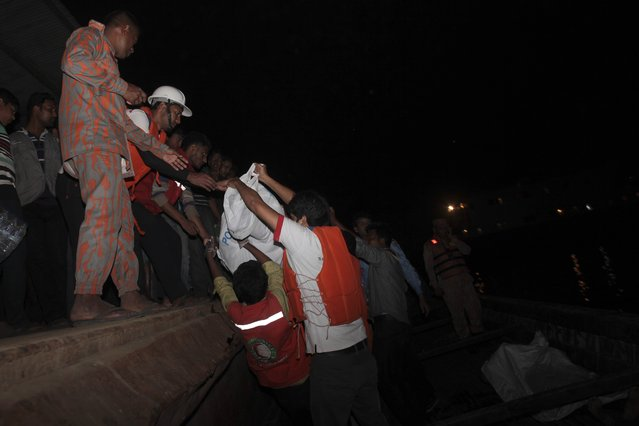 Bangladeshi rescue workers lift the dead body of one of the victims after a river ferry carrying about 100 passengers capsized Sunday after being hit by a cargo vessel,in Manikganj district, about 40 kilometers (25 miles) northwest of Dhaka, Bangladesh, Sunday, February 22, 2015. (Photo by A. M. Ahad/AP Photo)