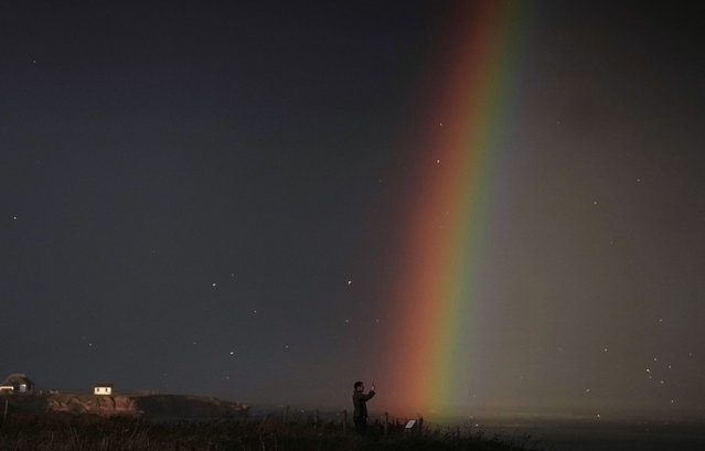 A ship passes by a rainbow off the coast at Tynemouth, United Kingdom on November 30, 2020. (Photo by Owen Humphreys/PA Images via Getty Images)