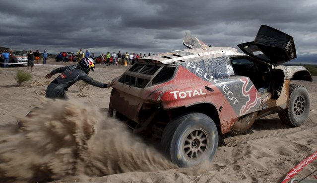 Cyril Despres of France tries to get his Peugeot out of the sand as co-pilot David Castera pushes the car during the 10th stage of the Dakar Rally 2016 near Fiambala, Argentina, January 13, 2016. (Photo by Marcos Brindicci/Reuters)