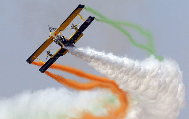 Skycat Wingwalkers from the Scandinavian Airshow aerobatic team perform on the forth day of Aero India 2015 at Yelahanka air base in Bangalore, India, Saturday, February 21, 2015. Aviation companies from around the world are participating in the five-day event which runs through Feb. 22. (Photo by Aijaz Rahi/AP Photo)