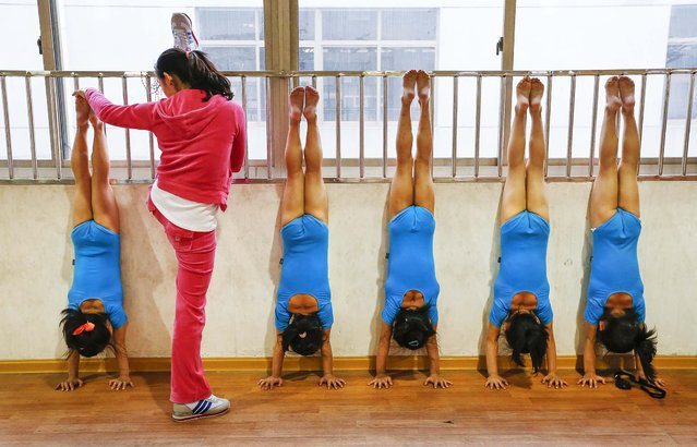 A teacher adjusts the position of a student as a group of first graders practice at the gymnastics hall of a sports school in Jiaxing, Zhejiang, on Oktober 15, 2013. The daily schedule for young gymnasts in the school includes literacy and general knowledge classes in the morning and athletic training in the afternoon. (Photo by William Hong/Reuters)