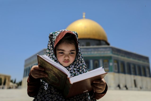 A girl sits with a holy book as the Dome of the Rock is seen in the background at the compound that houses al-Aqsa Mosque, known to Muslims as Noble Sanctuary and to Jews as Temple Mount, in Jerusalem's Old City on May 28, 2021. (Photo by Ammar Awad/Reuters)