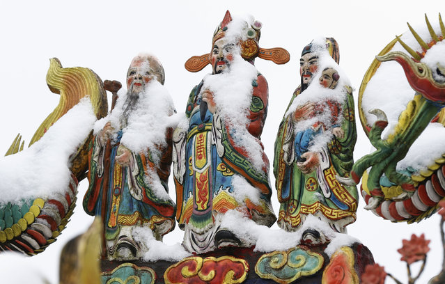 Snow sits on the Chinese god statues at the Pinglin temple in the high mountain area of New Taipei City, Taiwan, Monday, January 25, 2016. An unusually cold weather front that caused sudden drops in temperatures has been blamed for killing as many as 57 people in Taiwan's greater Taipei area. (Photo by Wally Santana/AP Photo)
