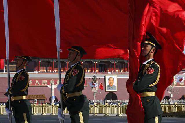 Members of an honor guard hold flags as they wait for the arrival of visiting Japanese Prime Minister Shinzo Abe during a welcome ceremony outside the Great Hall of the People in Beijing, Friday, October 26, 2018. (Photo by Andy Wong/AP Photo)
