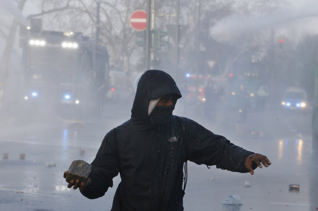 A protestor holds a stone as water cannons of the police approach Wednesday, March 18, 2015 in Frankfurt, Germany. (Photo by Michael Probst/AP Photo)