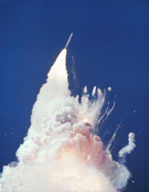 At about 76 seconds, fragments of the Orbiter can be seen tumbling against a background of fire, smoke and vaporized propellants from the External Tank. The left Solid Rocket Booster (SRB) flys rampant, still thrusting. The reddish-brown cloud envelops the disintergrating Orbiter. The color is indicative of the nitrogen tetroxide oxidizer propellant in the Orbiter Reaction Control System. (Photo by NASA)