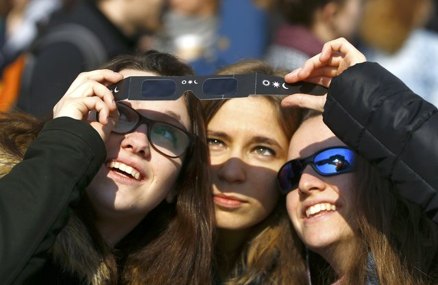 Italian pupils use a a pair of solar viewing glasses to observe a partial solar eclipse in Vienna March 20, 2015. (Photo by Leonhard Foeger/Reuters)