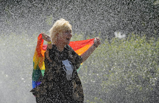 A woman with a rainbow flag cools off in a sprinkler ahead of the Equality Parade, the largest LGBT pride parade in Central and Eastern Europe, in Warsaw, Poland, Saturday, June 19, 2021. (Photo by Czarek Sokolowski/AP Photo)