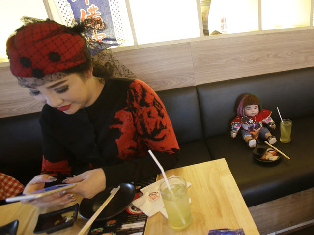 "Supavadee Tapmalai uses her smartphone next to a ""child angel"" doll at a Japanese restaurant in Bangkok, Thailand, Friday, January 28, 2016. (Photo by Sakchai Lalit/AP Photo)"