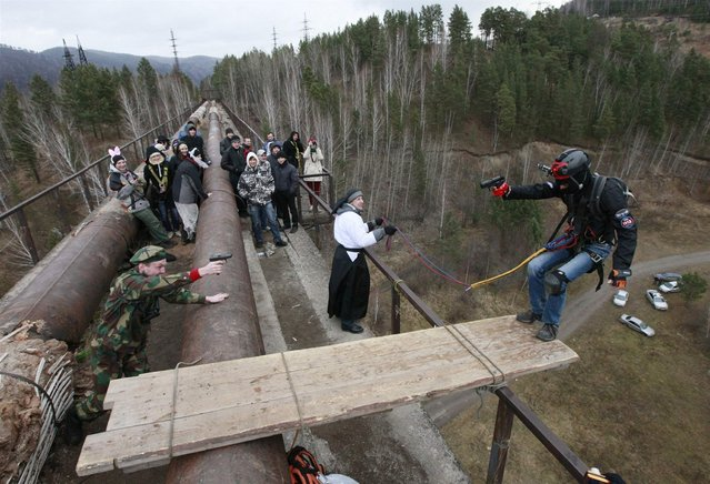 "Members of the ""Exit Point"" amateur rope-jumping group stage a performance as they jump from a 44-metre high (144-ft) waterpipe bridge in the Siberian Taiga area outside Krasnoyarsk, November 3, 2013. Fans of rope-jumping, a kind of extreme sport involving a jump from a high point using an advanced leverage system combining mountaineering and rope safety equipment, marked the end of the group's jumping season and recent Halloween festivities. (Photo by Ilya Naymushin/Reuters)"