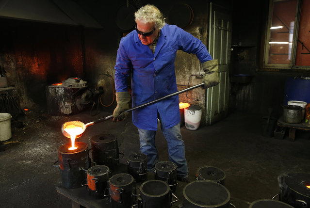 Serge Huguenin of the Blondeau foundry pours the metal into the mould during the preparation of the Rio 2016 bronze bells in La Chaux-de-Fonds, Switzerland January 21, 201. (Photo by Denis Balibouse/Reuters)