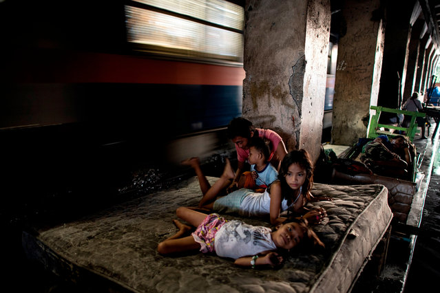 This picture taken on October 17, 2018 shows a family living along a train track in Manila, Philippines. (Photo by Noel Celis/AFP Photo)