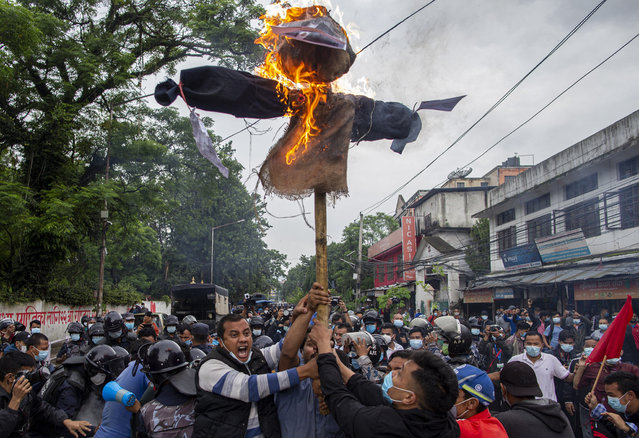 Nepalese protestors affiliated with wings of main opposition political parties burn an effigy of Nepalese president Bidhya Devi Bhandari and Prime Minister K.P. Sharma Oli during an anti-government protest in Kathmandu, Nepal, 01 July 2021. Nepalese student activists protested amidst Coronavirus lockdown, against Prime Minister KP-Oli government's act of dissolving the House of Representatives. (Photo by Narendra Shrestha/EPA/EFE)
