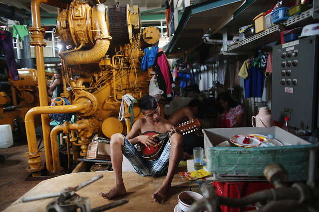 A boy plays a guitar in the hull of a tanker that was washed ashore in a particularly badly damaged part of Tacloban during Typhoon Haiyan on November 19, 2013 in Leyte, Philippines. (Photo by Dan Kitwood/Getty Images)