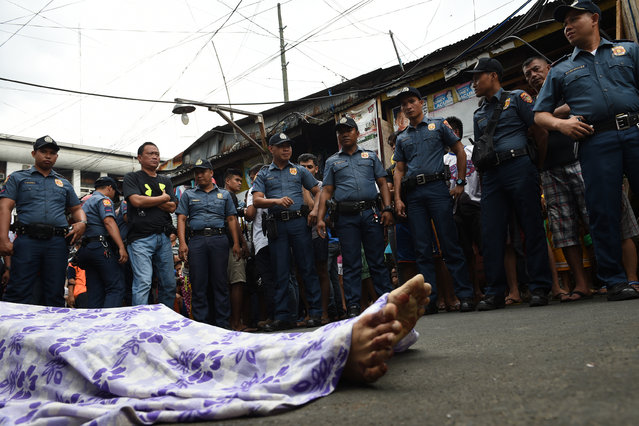 Policemen gather over the body of a suspect killed during an anti-drug operation at an informal settlers' area near a port in Manila on November 10, 2016. Philippine President Rodrigo Duterte's war on drugs and other crimes took he office on June 30 has claimed 4,447 lives, according to official figures made available by police on November 10. (Photo by Ted Aljibe/AFP Photo)