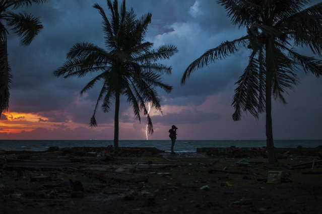A photojournalist is silhouetted by the sunset as a lightning strike at a resort affected by Saturday's tsunami in Carita, Indonesia, Tuesday, December 25, 2018. Christmas celebrations traditionally filled with laughter and uplifting music were replaced by somber prayers for tsunami victims in an area hit without warning following a volcanic eruption, leaving hundreds of people dead and thousands homeless in disaster-prone Indonesia. (Photo by Fauzy Chaniago/AP Photo)