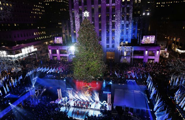 The Rockefeller Center Christmas tree towers over the skating rink in New York. Some 45,000 energy efficient LED lights adorn the 76-foot tree. (Photo by Kathy Willens/Associated Press)