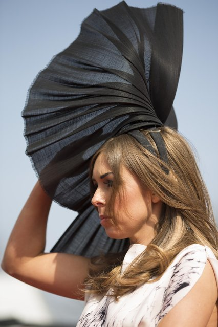 A spectator holds her hat on in the breeze during Aintree race meeting's Ladies Day the day before the Grand National horse race at Aintree Racecourse Liverpool, England, Friday, April 10, 2015. (Photo by Jon Super/AP Photo)